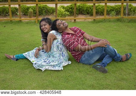 One Indian Married Couple Sitting On The Grass And Enjoying Their Time Together. Concept Of Love And