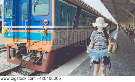 Young Female Tourist Wearing Mask Walking To A Train Station And Looks At A Tourist Map For Travel I