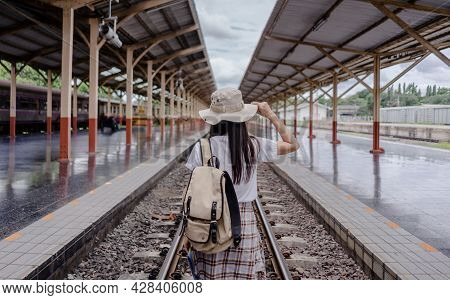 Traveler Woman Tourist Hand Holding Hat And Backpack And Holding Tourist Map Walking On The Railway
