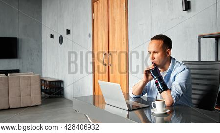 Thoughtful cyborg programmer with black bio hand prothesis looks at laptop screen solving problem sitting at table with cup of coffee in room