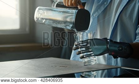 Disabled guy with bio hand prothesis pours water into glass from bowl and drinks standing in kitchen with window at home close view