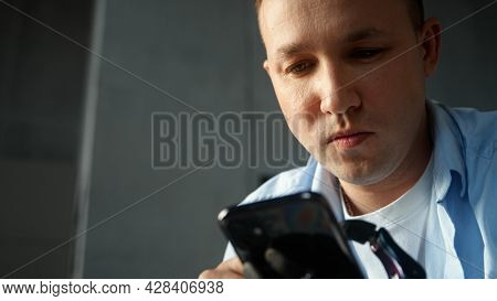 Concentrated man in blue shirt types on smartphone holding device in black artificial limb hand prothesis at home close view