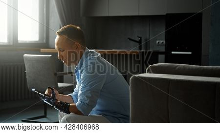 Concentrated disabled guy cyborg types and switches on smartphone holding in black bio hand prothesis sitting on large sofa at home