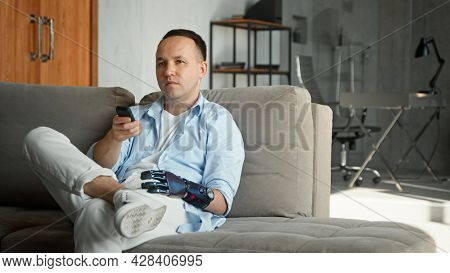 Relaxed man with high tech bio hand prothesis takes remote controller and switches television channels sitting on large sofa at home