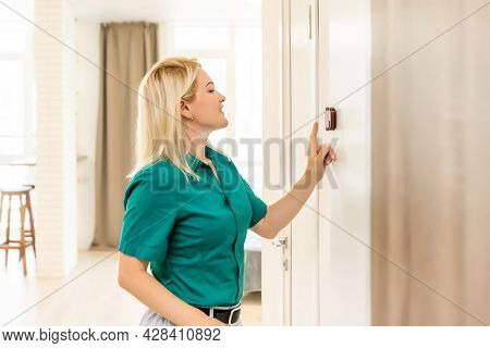 Woman Regulating Heating Temperature With A Modern Wireless Thermostat Installed On The White Wall A