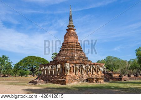 View Of The Ancient Chedi With Sculptures Of Elephants On A Sunny Day. Ruins Of The Buddhist Temple