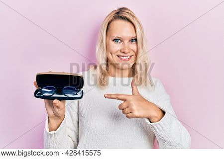 Beautiful caucasian blonde woman holding glasses in eyewear case smiling happy pointing with hand and finger