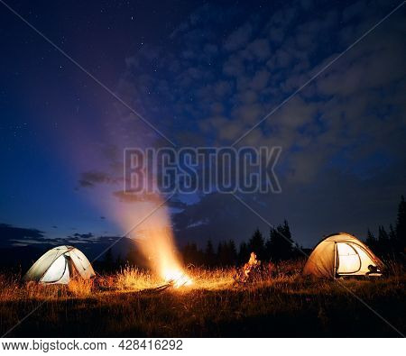 Beautiful View Of Night Sky With Stars With Illuminated Camp Tents, Campfire And Hikers. Tourists Cu