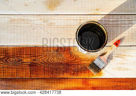 Brush For Covering Wood And Varnish In A Jar On A Wooden Surface. Protecting Wood From Water, Varnis