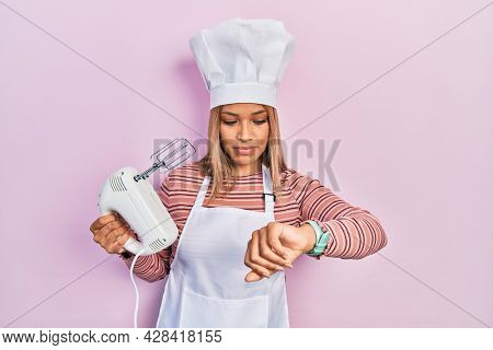 Beautiful hispanic woman holding pastry blender electric mixer checking the time on wrist watch, relaxed and confident