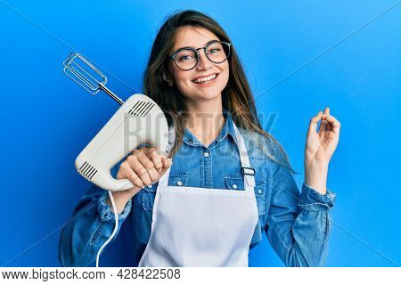 Young caucasian woman holding pastry blender electric mixer smiling happy pointing with hand and finger to the side