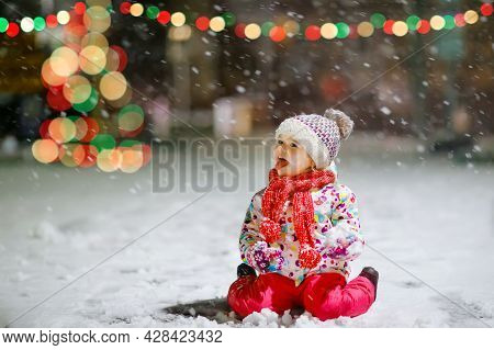 Adorable Little Toddler Girl Walking Outdoors In Winter. Cute Toddler During Strong Snowfall On Even