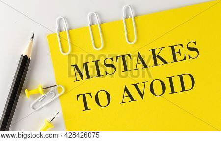 Mistakes To Avoid Word On The Yellow Paper With Office Tools On White Background
