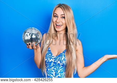Young caucasian woman holding shiny disco ball celebrating achievement with happy smile and winner expression with raised hand