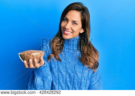 Young latin woman holding bowl with lentils looking positive and happy standing and smiling with a confident smile showing teeth