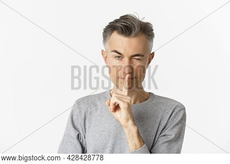 Close-up Of Cheeky Handsome, Middle-aged Man, Winking And Making Hush Sign, Asking To Keep Secret Or