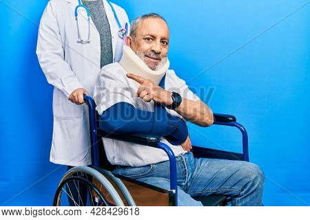 Handsome senior man with beard sitting on wheelchair with neck collar cheerful with a smile on face pointing with hand and finger up to the side with happy and natural expression