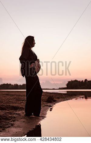 Pregnant Woman On Beach At Sunset. Silhouette In Profile Against Background Of Setting Sun Of Beauti