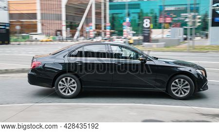 Moscow, Russia - April 2021: Black Mercedes Benz E Class W212 Driving On The City Road. Man Using Ce