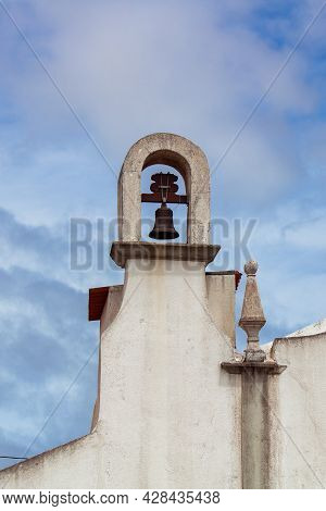 Detail Of Small Bell Tower And Pinnacle On Top Of Portuguese Christian Chapel Against The Cloudy Blu