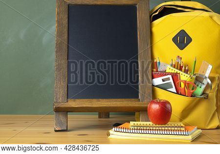 School Supplies In A Backpack With A Chalkboard On Wooden Table