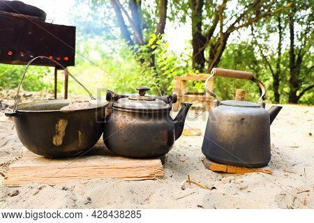 Camping Utensils In Soot Stand Near A Hot Barbecue On A Wooden Board In The Forest. Dishes Covered I