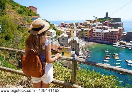 Summer Holiday In Italy. Back View Of Young Woman With Backpack And Hat Looking At Vernazza Village,