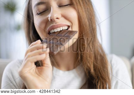 Cheerful Young Woman Eating Chocolate At Home