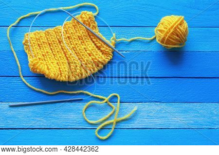 Knitting, Hobbies Concept.  Yellow Knitted Cloth With Knitting Needles And Ball Of Wool  On  Blue Ru