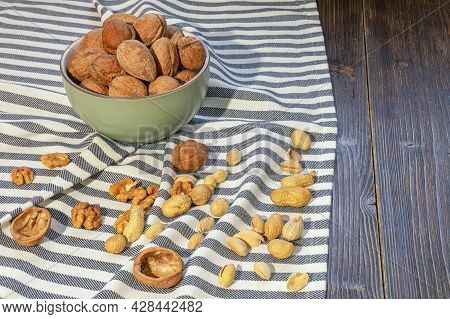 Nuts On Dark Rustic Table. Whole Walnuts And Kernels, Pistachios, Peanut. Copy Space