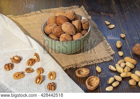 Nuts. Whole Walnuts And Kernels On Dark Rustic Table