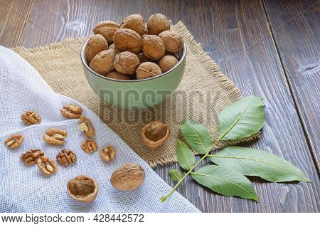 Whole Walnuts And Kernels On Dark Rustic Table.  Leaves Of Walnut Tree