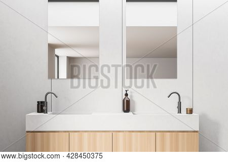 Closeup View Of Wooden Vanity With White Top, Having Two Sinks, Two On-trend Faucets And Two Vertica