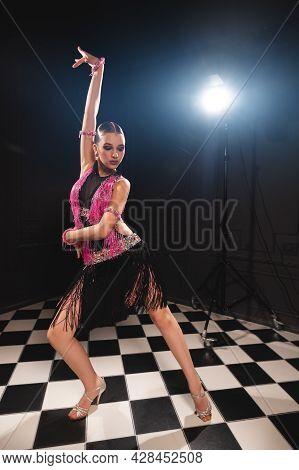 Young Attractive Girl In A Black Pink Dress In A Dark Room Studio Is Dancing Latin American Dances.