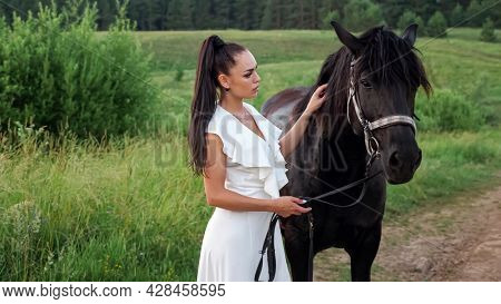 Young Woman Brunette With Long Hair In Ponytail Pets Black Horse And Animal Shakes Head Standing On