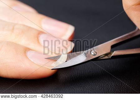 Home Nail Care. A Girl Cuts A Fragile Broken Nail. Brittle Nail Concept