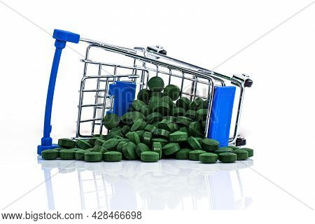 Upside Down Cart With Scattered Spirulina Pills Isolated On White