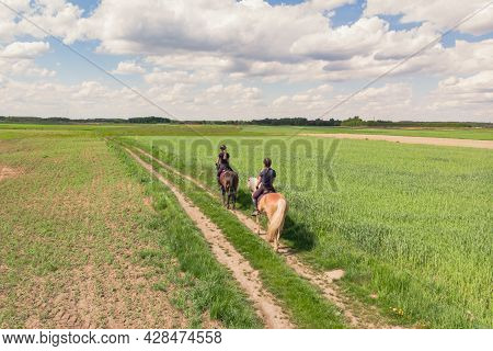 Two Horse Riders On A Flaxen Horse And A Dark Bay Horse Moving Across The Beautiful Farm Field Durin