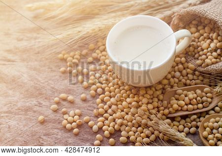 Home Made Delicious Soybean Milk In Soft Yellow Cup With Dry Soybean Seed In Sack And Wooden Spoon O