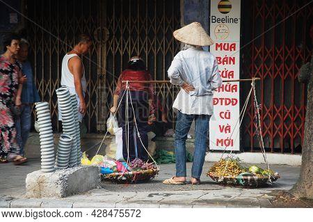 Old Vietnam Woman Street Vendors Bearing Hawker Basket Walking Sale Local Food Product To Vietnamese