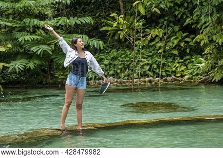 Adventure Summertime Lifestyle Leisure Holiday Concept. Traveler Young Woman Standing On Rock Blue P