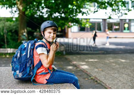 Happy Little Kid Boy With Satchel And Bicycle Helmet. Schoolkid On The Way To Middle Or High School.