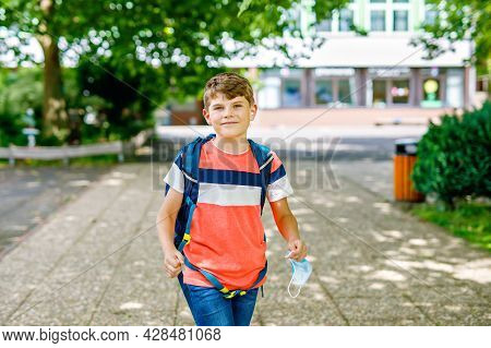 Kid Boy With Medical Mask On The Way To School. Child With Backpack Satchel. Back To School After Su