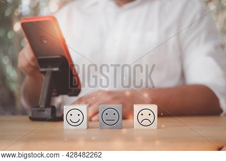 Wood Blocks With The Face Symbol On The Table With Man Use Mobile Phone For Satisfaction Assessment.