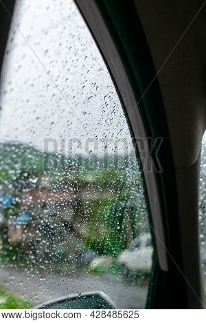 Raindrops On The Window Door Glass Of The Car During Monsoon Rainy Season. Used Selective Focus With