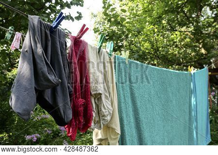 Different Washed Clothes Is Dried On Rope In Backyard Or Garden. Drying Linen With Multicolored Clot