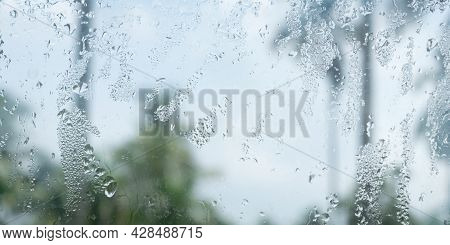 Rain Drops On Glass Window. Raindrops Falling From Glass Material. Abstract Nature Background. Copy