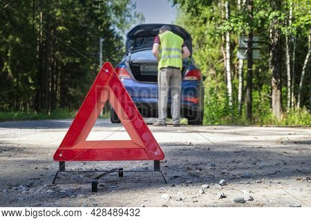 A Portable, Reflective Red Warning Sign Stands On The Side Of The Road Next To The Damaged Vehicle.