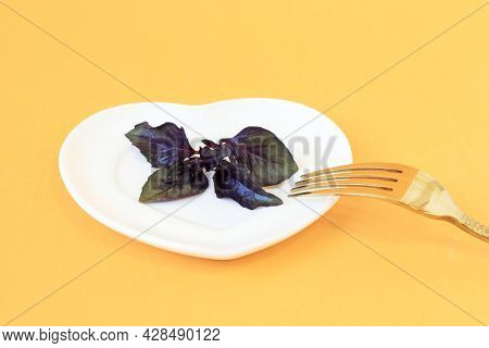 The Concept Of Proper Nutrition. Salad On A Heart-shaped Plate, Fork, Yellow Background, Space For T