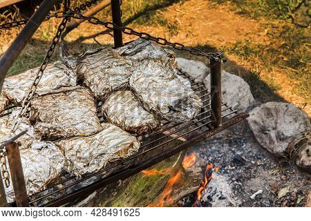 Meat Grilled In Foil On Flaming Bbq Grill. Barbecue Cooking Flaming Grill Grid Food Background In Al